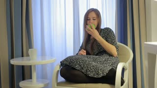 Pretty girl bite off apple seating in armchair