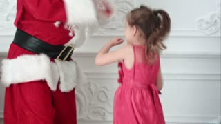 Pretty little girl dancing together with Santa Claus