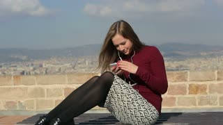 Pretty woman listen music by phone relax on bench