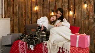 Pretty young mom reading a Christmas tale to her cute daughter sitting on the sofa wrapped in blankets