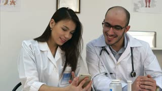 Pretty young nurse showing something funny on her phone to male colleague