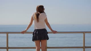 Rear view of a thoughtful beautiful young woman in blue skirt contemplating the sea on a beach on a summer holiday, outdoors. Teenager travel lifestyle.