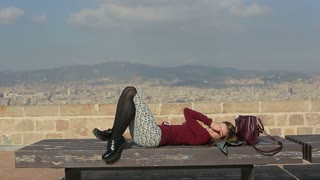 relaxed woman lay on bench top of city