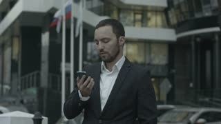Russian businessman answering call by phone and explain something to business partners, standing outside the office