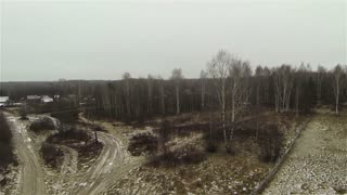 Russian forest during fall and a small settlement. View from the helicopter.