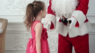 Santa and pretty little girl having fun and dancing