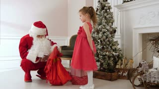 Santa Claus giving presents to a pretty little girl and hugging her