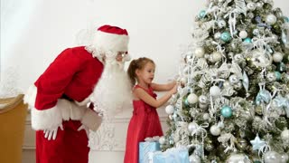 Santa Claus helping pretty little girl to decorate Christmas tree