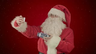 Santa Claus holding a big present doing a selfie on smartphone on red background with snow