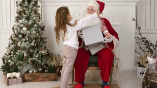 Santa Claus holding presents and hugging a little cute girl