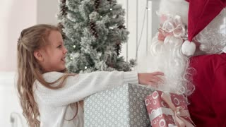 Santa Claus hugging a little cute girl and giving her Christmas present