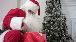 Santa Claus opening his sack and putting presents under the Christmas tree