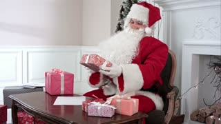 Santa Claus preparing presents for children and checking the gift list