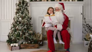Santa Claus reading a book with cute girl near the Christmas tree