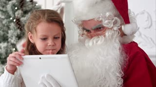 Santa Claus taking Christmas selfie on tablet with cute little girl sitting on his lap