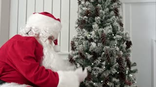 Santa Claus taking presents out of his bag uner the Christmas tree