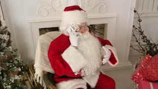 Santa Claus talking over the phone wishing Merry Christmas