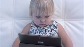 Serious baby girl looking at tablet