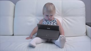 Serious baby girl playing with tablet