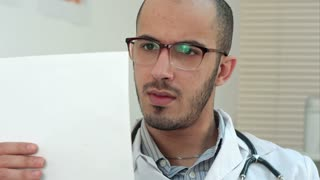 Serious doctor checking important medical analysis