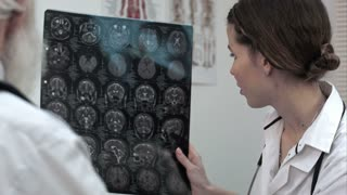 Serious doctor man showing results of magnetic resonance imaginig to a senior patient.