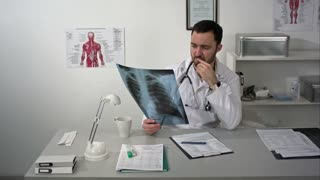 Serious medical doctor sitting at table and looking patients x-ray