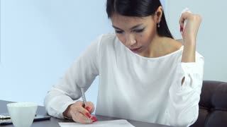 Sick business woman sneezing and blowing her nose while signing papers in a cafe