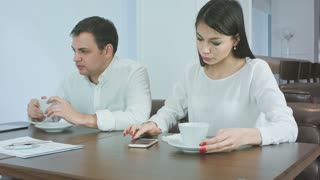 Sick businessman sneezing while anxious female checking his head for fever and giving him napkin