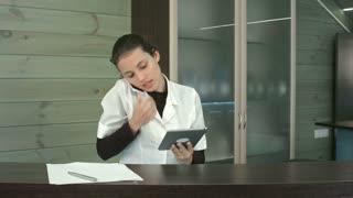 Smiling beauty salon manager talking on the phone while using tablet and taking notes at the reception desk