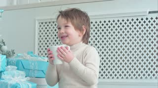 Smiling boy in white jumper drinking tea next to the Christmas tree