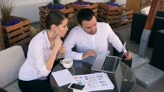 Smiling businesspeople with laptop outdoors in cafe