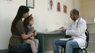 Smiling doctor explaining cardiogram to mother and little girl