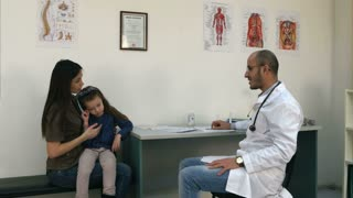 Smiling doctor giving bunny toy to cheer up upset little girl patient