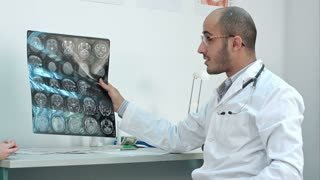 Smiling doctor showing brain computed tomography x-ray image to his patients