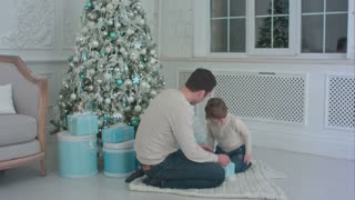 Smiling father and his happy son opening presents sitting next to the Christmas tree