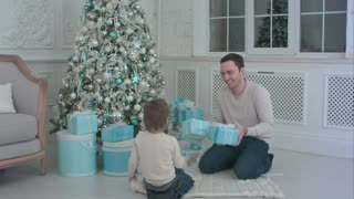 Smiling father and his son opening Christmas presents in the living room