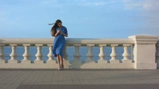 Smiling girl in blue dress texting message