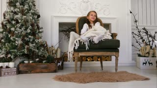 Smiling girl wrapped in a blanket sitting on a cozy chair and waiting for Santa