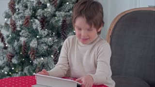 Smiling kid boy sitting on a chair and playing with tablet during Christmas time
