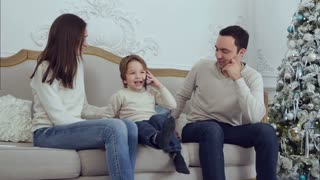 Smiling little boy talking on the phone surrounded by his happy family