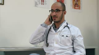 Smiling male doctor having a cheerful phone conversation