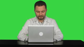 Smiling male doctor sitting at table with laptop on a Green Screen, Chroma Key