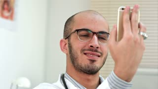 Smiling male doctor taking selfies on his phone