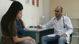 Smiling male doctor talking with shy little girl sitting on her mother's laps