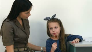 Smiling mother talking to her little girl eating a lollipop at doctor's office