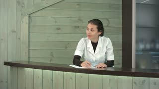 Smiling spa receptionist greeting a female customer and telling her about services