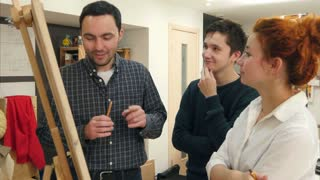Smiling students and female art teacher analyzing artwork on easel