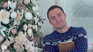 Smiling young man holding a book standing next to a Christmas tree