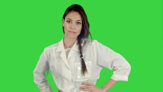 Smiling young woman in lab coat making funny dance on a Green Screen, Chroma Key