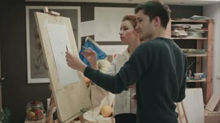 Student and art teacher during painting lesson